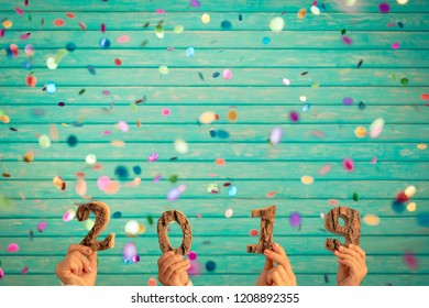 Happy New Year 2019! Confetti falling against wooden background
