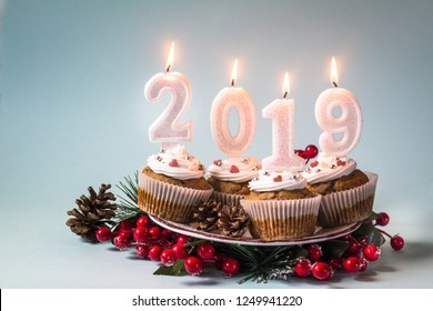 Happy New Year 2019 cupcakes with lighting candles on blue background. Merry Christmas and winter season greetings concept. Copy space