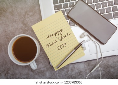 Happy New Year 2019 greeting concept. Notes, laptop, coffee, earphones, pen; element of young generation.