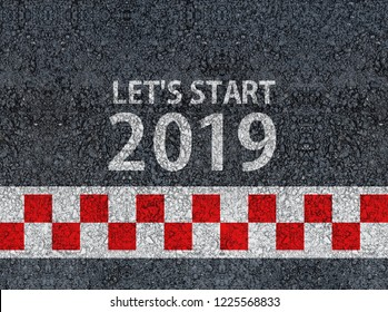 happy new year 2019. lets start 2019 and racing start line written on an asphalt road