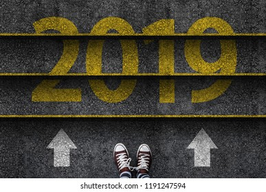 happy new year 2019. man legs in sneakers standing next to stairs with number 2019