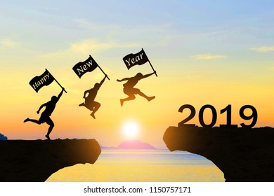 Happy New Year 2019 Men jump over silhouette mountains and sun