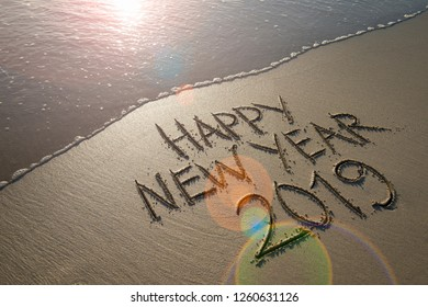 Happy New Year 2019 message handwritten in smooth sand with sunrise lens flare over oncoming wave on the beach