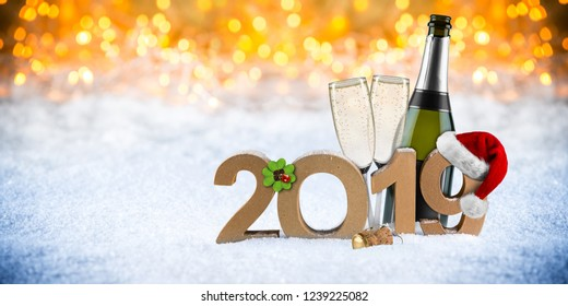 happy new year 2019 number with santa hat four leaf clover champagne bottle glass in front of golden bokeh lghts panorama snow background