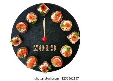 Happy New Year 2019! Smoked salmon canapes on black slate platter form a clock face showing midnight.