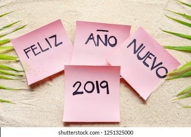 "Happy new year 2019 in spanish ""Feliz año nuevo 2019"" on the sand"