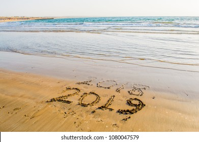 Happy New Year 2019 text on the sea beach. Abstract background photo of coming New Year 2019 and leaving year of 2018