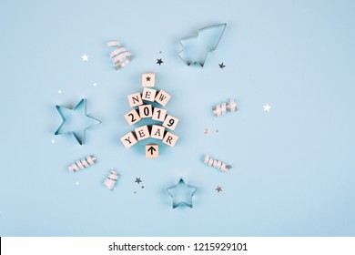 Happy New Year 2019 text made as Christmas tree with wooden cubes. Sparkles and shapes for gingerbread on blue pastel background. Flat lay style. Concept of celebrating new year. Christmas mood.