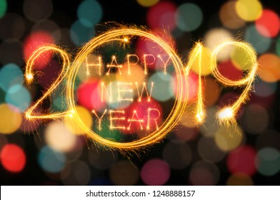 Happy new year 2019 text written with Sparkle fireworks isolated on colourful light bokeh background