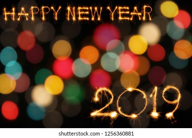Happy new year 2019 text written with Sparkle fireworks with blurred color lights bokeh bacground
