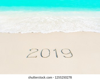 Happy New Year 2019 travel season concept on azure tropical sandy beach - winter vacation in hot countries background