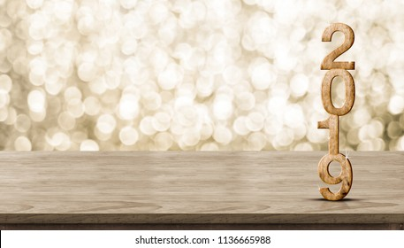 Happy New Year 2019 wood with sparkling star on brown wood table with gold bokeh background,Holiday festive celebration concept.Banner mock up for display of product or design content
