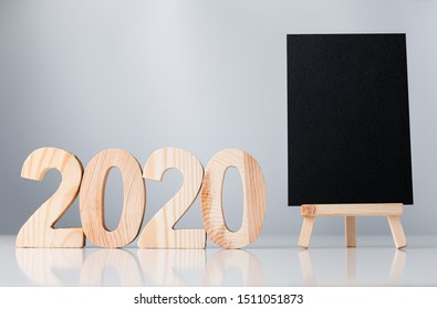 happy new year 2020 with blackboard on white table and grey background.holiday celebration