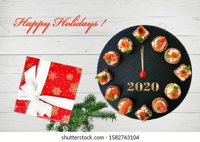 Happy New Year 2020! Clock face showing 12 o'clock, creative food idea with smoked salmon canapes and gift over white wooden background.