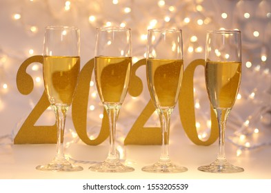 Happy New Year 2020,  Four (4) Filled Champagne Glasses and Blurry   Number 2020 and Lights in Background