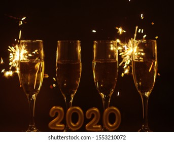 Happy New Year 2020, Four (4) Filled Champagne Glasses,  Blurry  Number 2020 in Front and Sparkles Behind on Black