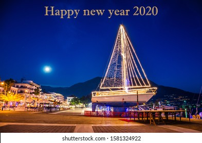 Happy new year 2020 inscription with a traditional decorated boat in Greece. New years eve concept