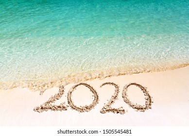 Happy New Year 2020, lettering on the beach with wave and clear blue sea. Numbers 2020 year on the sea shore, message handwritten in the white sand on beautiful beach background. New Years concept.