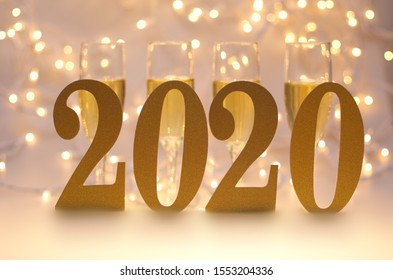 Happy New Year 2020, Number 2020 and Blurry Four (4) Champagne Glasses and Lights in Background