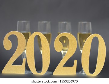 Happy New Year 2020, Number 2020 and Four (4) Blurry Champagne Glasses on Black