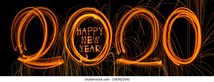 Happy New Year 2020. Number 2020 written sparkling sparklers isolated on black background With Copy Space For Text. Beautiful Glowing overlay template for holiday greeting card.