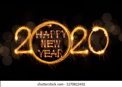 Happy new year 2020 text written with Sparkle fireworks isolated on luxury gold bokeh background
