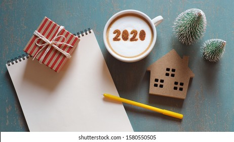Happy new year 2020 theme white coffee cup with number 2020 on frothy surface over green background with house model, gift box, Christmas trees, yellow pen and blank notebook paper. (top view)