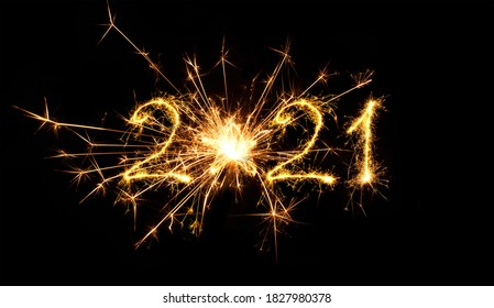 Happy New Year 2021. Creative Number 2021 with sign star written sparkling sparklers isolated on black background. Beautiful Glowing overlay object for design holiday greeting card.