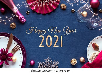 Happy New Year 2021 gilded text in frame made from Silvester party table setup. Vine, glasses, plates, fork, knife. Xmas decorations and garland. Flat lay in golden and red on classic blue textile.