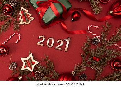 Happy New Year 2021. Golden digits 2021 with christmas hat are on red background with glitter. Holiday Party Decoration or postcard concept with top view and copy space