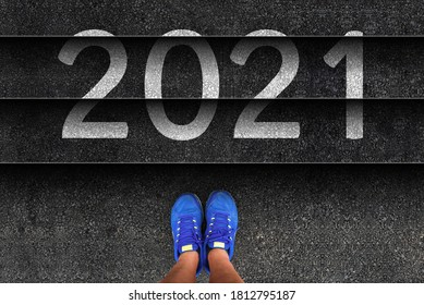 happy new year 2021. man legs in sneakers standing next to stairs with number 2021
