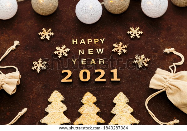 Happy new year 2021 on the chocolate background in a handmade style. Garland, snowflakes, Christmas trees, wooden letters and numbers, gifts in bags for zero waste.