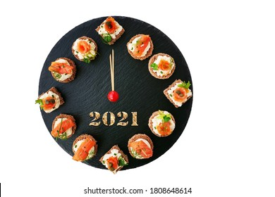 Happy New Year 2021! Smoked salmon canapes on black slate platter form a clock face showing midnight isolated
