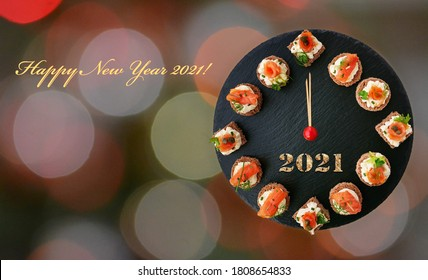 Happy New Year 2021! Smoked salmon canapes on black slate platter form a clock face showing midnight over bokeh background