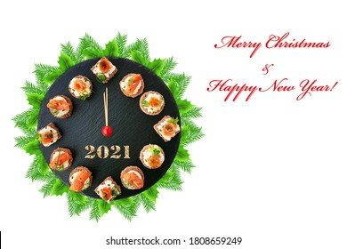 Happy New Year 2021 Smoked salmon canapes on black slate platter form a clock face showing midnight over a fir tree wreath isolated