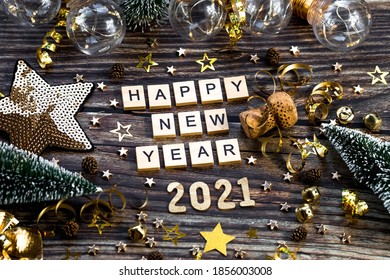 Happy New Year 2021. A symbol from the number 2021 with Golden balls, stars, sequins and a beautiful bokeh on a wooden background. The concept of the celebration. - Shutterstock ID 1856003008
