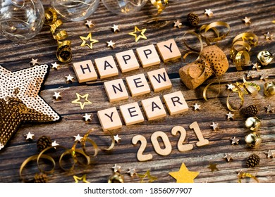 Happy New Year 2021. A symbol from the number 2021 with Golden balls, stars, sequins and a beautiful bokeh on a wooden background. The concept of the celebration. - Shutterstock ID 1856097907