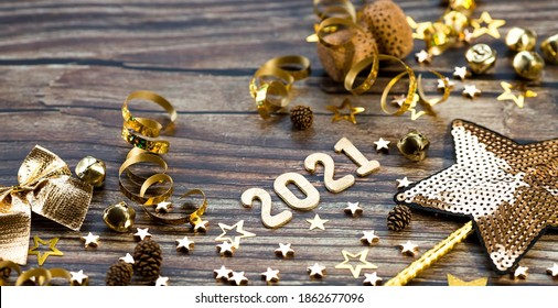 Happy New Year 2021. A symbol from the number 2021 with Golden balls, stars, sequins and a beautiful bokeh on a wooden background. The concept of the celebration.