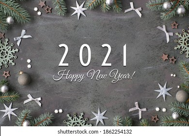 Happy New Year 2021 text. Flat lay background in silver, grey and green. Top view with fir twigs decorated with trinkets stars, hearts, bows and snowflakes.