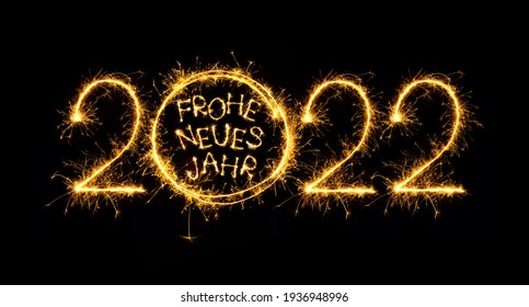 Happy New Year 2022. Creative lettering Frohe Neues Jahr 2022 translated from German language Happy New Year 2022 written burning sparklers on black background. Beautiful sparkling template for design