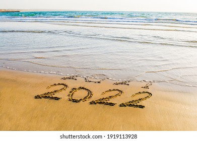 Happy New Year 2022 text on the sea beach. Abstract background photo of coming New Year 2022 and leaving year of 2021