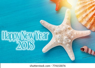 Happy New year background with shells, starfish on a wooden blue background