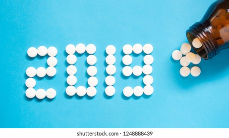 Happy New Year banner for medical theme. Number 2019 made by white pills/tablets spilling out of brown glass bottle on blue background. Creative idea for health care, medical and pharmacy concept.