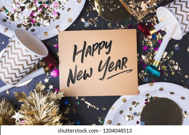 Happy new year brush stroke handwriting on golden greeting card with party cup,party blower,tinsel,confetti.Holiday celebrate party time.top view tabletop