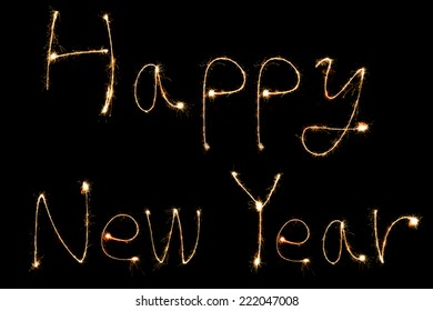 happy new year ! burning sparkler stick and writing sparkling text on black background