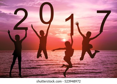 Happy new year card 2017. Silhouette of children girl jumping on tropical beach with fantastic sunset sky background. Kids holding the number 2017 with sea and sunrise background.