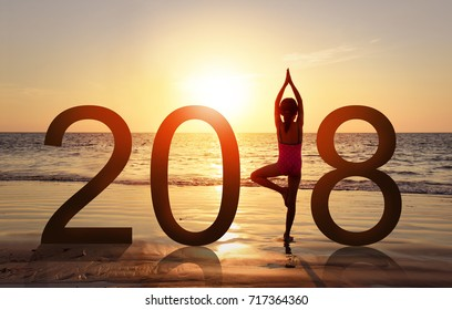 Happy new year card 2018. Silhouette of A girl doing Yoga vrikshasana tree pose on tropical beach with sunset sky background, watching the sunset, standing as a part of the Number 2018 sign.