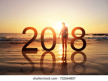 Happy new year card 2018. Silhouette of healthy young woman standing on the beach watching sunset or sunrise, girl in swimming suit looking the rising sun, stand as a part of the Number 2018 sign.
