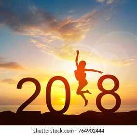 Happy new year card 2018. Silhouette of young girl jump on top of mountain with fantastic sea and sunrise sky. Happy joyful girl jumping as a part of the Number 2018 sign with rising sun background.
