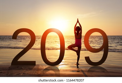 Happy new year card 2019. Silhouette of healthy girl doing Yoga vrikshasana tree pose on tropical beach with sunset sky background, watching the sunset, standing as a part of the Number 2019 sign.